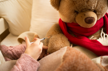 sick teddy bear: Closeup photo of little girl doing injection to sick teddy bear