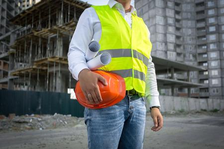 GERENTE: Arquitecto en la chaqueta amarilla de seguridad que presenta con el casco rojo en el sitio de construcción