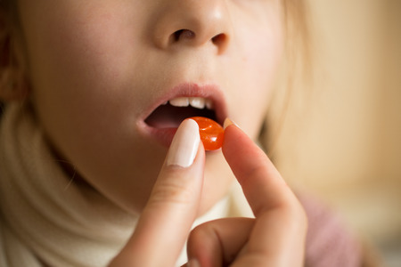 pill: Macro photo of little sick with flu girl taking pill in mouth Stock Photo