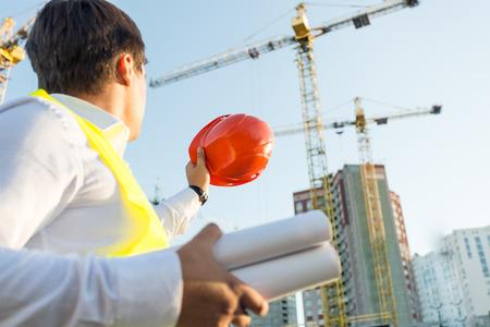 Detailním fotografie inženýra představuje na staveništi s oranžovou přilba