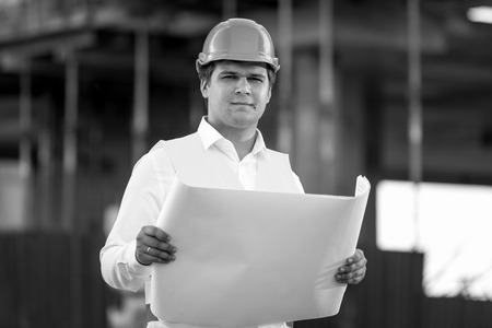 foreman: Black and white portrait of foreman posing with documents and blueprints against unfinished building