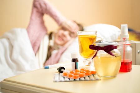 ragazza malata: Vaso con miele, tazza di tè e farmaci che si trovano sul tavolo accanto al letto malata Archivio Fotografico