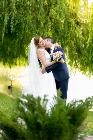 passionately: Beautiful bride and groom passionately kissing under tree at river Stock Photo