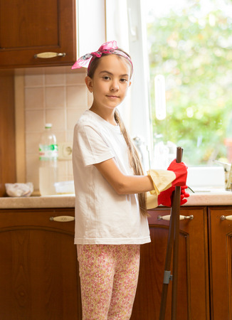 messy kitchen: Portrait of smiling girl posing on messy kitchen with broom and scoop Stock Photo