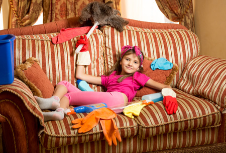 Funny photo of exhausted girl relaxing on sofa after cleaning house Фото со стока
