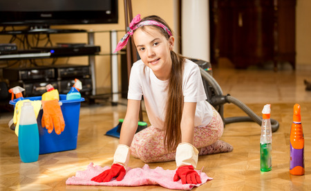 cleaning up: Cute smiling teenage girl cleaning up living room and washing wooden floor Stock Photo