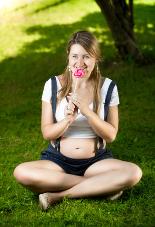 women s health: Cute pregnant woman sitting on grass at park and licking candy