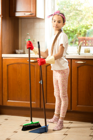 domestic task: Cute girl in rubber gloves sweeping floor at kitchen with swab and scoop