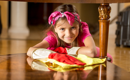 rubber gloves: Cute smiling girl in rubber gloves cleaning table by rag Stock Photo