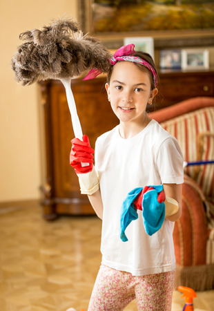 domestic task: Portrait of smiling girl helping with housework and cleaning