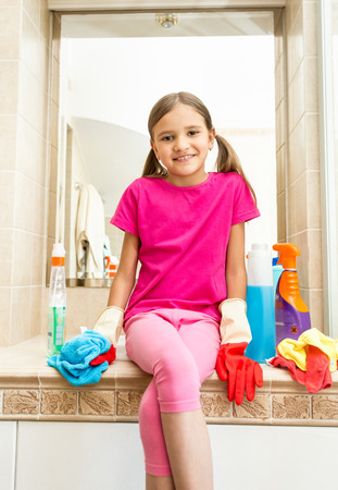 tidying up: Portrait of smiling girl sitting on sink at bathroom while doing cleaning