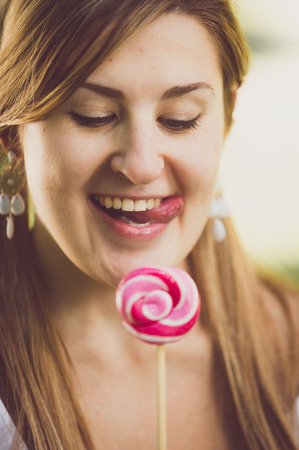 sugarplum: Closeup toned portrait of cute funny woman licking her lips at lollipop Stock Photo
