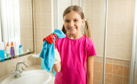 Portrait of cute girl doing cleaning posing with blue rag Фото со стока