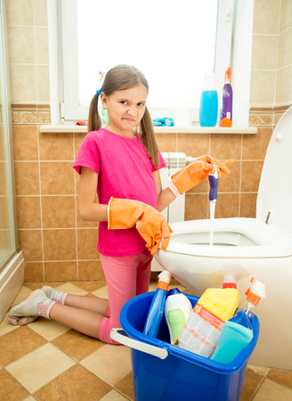 revulsion: Cute girl cleaning toilet with disgust Stock Photo