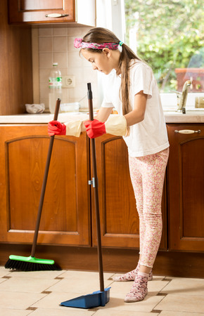 household tasks: Little brunette girl cleaning floor on kitchen with broom and scoop