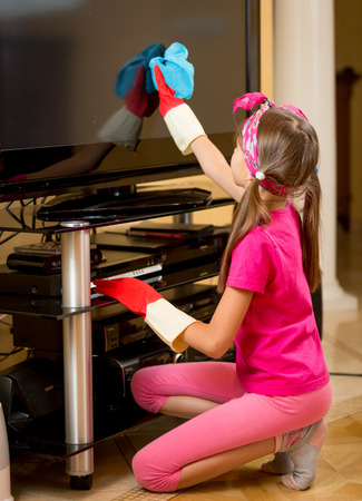 rubber gloves: Little girl in rubber gloves cleaning TV screen from dust with blue cloth