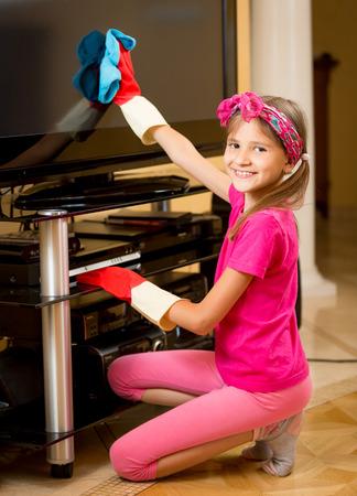 big screen tv: Portrait of smiling girl doing housework an cleaning big TV screen