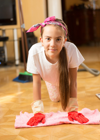 floor cloth: Closeup portrait of smiling teenage girl washing floor with cloth Stock Photo