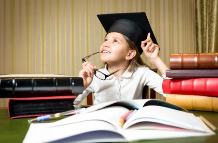 GRADUADO: Retrato de niña pensativa inteligente posando en el escritorio en la tapa de graduación Foto de archivo