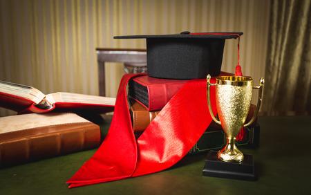 primer lugar: Foto del primer del sombrero de la graduación, cinta roja y copa de oro para el primer lugar