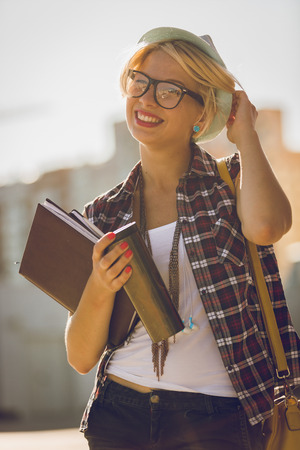 Toned portrait of hipster girl on street with notebook and cup of coffee