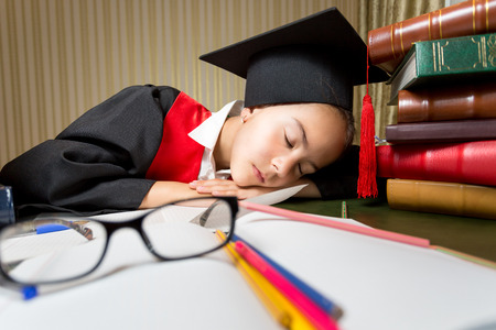 seeping: Portrait of tired girl in graduation cap seeping at library table