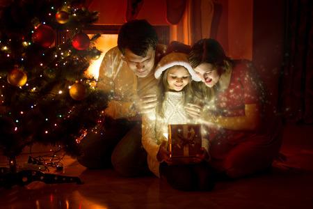 fiesta familiar: Familia feliz que mira el interior de la caja de regalo mágico de la Navidad