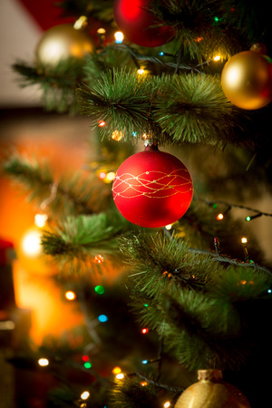 Closeup photo of red Christmas ball on fir tree next to fireplace Фото со стока