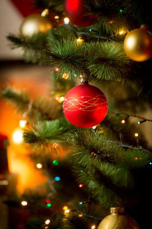Closeup photo of red Christmas ball on fir tree next to fireplace Standard-Bild