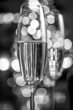Macro black and white photo of two champagne glasses on background of Christmas lights