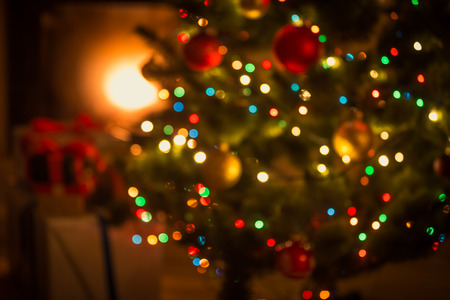Blurred background of decorated glowing Christmas tree and fireplace