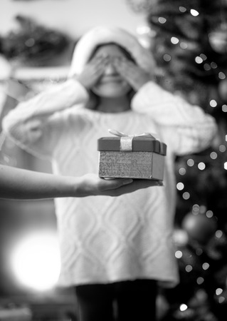 desaturated: Black and white conceptual photo of mother making daughter a surprise on Christmas