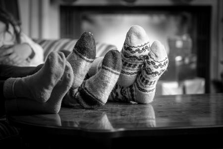 Closeup black and white photo family wearing woolen socks warming at fireplace Foto de archivo