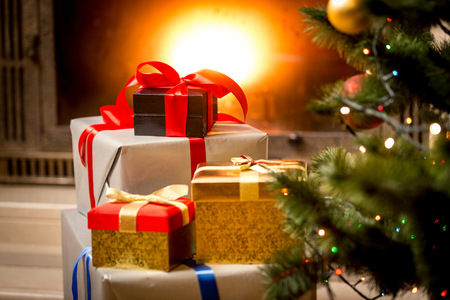 Stack of packed gift boxes under Christmas tree at fireplace Archivio Fotografico