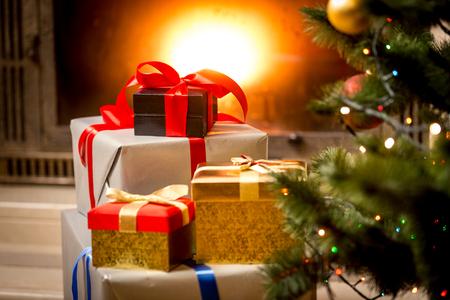 Pila di scatole regalo confezionati sotto l'albero di Natale al camino