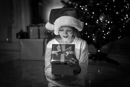 looking inside: Black and white portrait of happy amazed girl looking inside of Christmas present