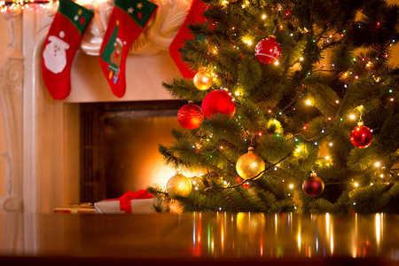 new ball: Christmas holiday background of wooden table against decorated Christmas tree and fireplace Stock Photo