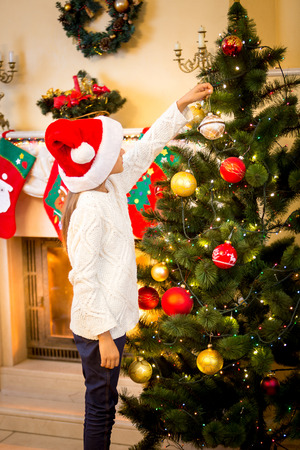 woman hanging toy: Little girl hanging decorative ball on Christmas tree Stock Photo