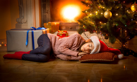 Cute girl sleeping on floor under Christmas tree next to fireplace