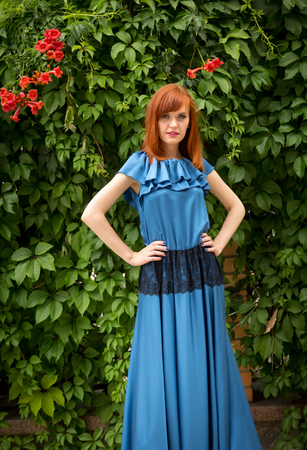 ivy wall: Portrait of elegant redhead woman in long blue dress posing against ivy wall