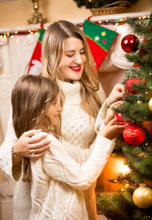 decorate: Portrait of happy mother and daughter decorating Christmas tree at house Stock Photo