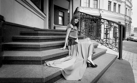 desaturated: Black and white photo of elegant woman in long dress sitting on stone stairs