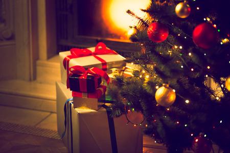 Tónovaný fotografie zdobené vánoční strom a dárkové krabičky proti hořícím krbem Reklamní fotografie