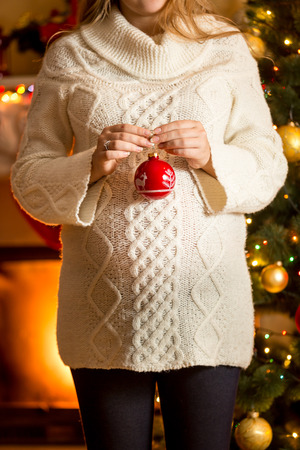 bow belly: Closeup photo of pregnant woman posing against fireplace with Christmas ball