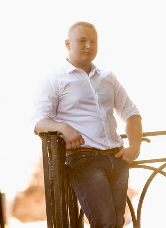 cerveza negra: Enton� el retrato del hombre con estilo stout en camisa apoy�ndose en barandas de metal