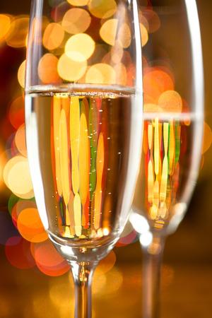 sektglas: Macro photo of two champagne glasses shot against sparkling Christmas tree lights