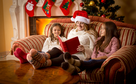 Happy woman reading book to daughters on sofa at fireplace at Christmas
