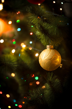 Macro photo of golden ball and light garland on Christmas tree