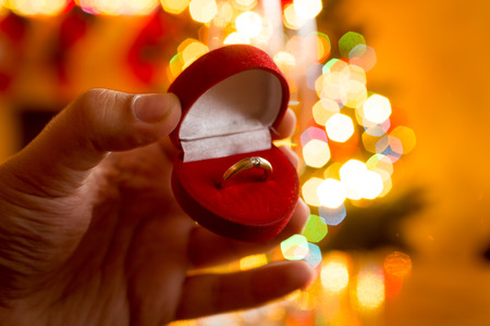 gold ring: Macro photo of man presenting golden ring in box against decorated Christmas tree