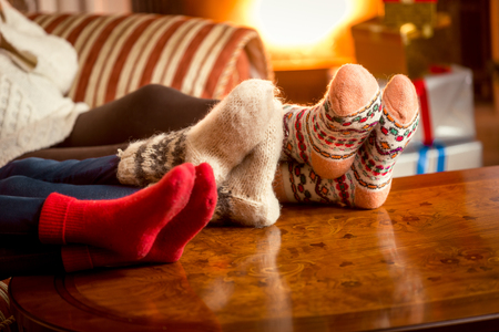 Closeup conceptual photo of family warming feet at fireplace Stock Photo